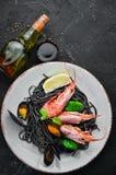 Spaghetti neri Paste nere con frutti di mare ed il limone Gamberetto e cozze Sui vecchi precedenti immagine stock