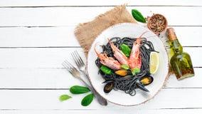 Spaghetti neri Paste nere con frutti di mare ed il limone Gamberetto e cozze Sui vecchi precedenti fotografie stock