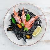 Spaghetti neri Paste nere con frutti di mare ed il limone Gamberetto e cozze Sui vecchi precedenti fotografia stock libera da diritti