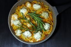 Spaghetti nests with chiken meatballs and sour cream sauce on dark table stock photo
