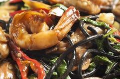 Spaghetti noirs épicés avec des crevettes roses Images stock
