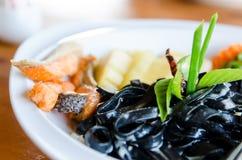 Spaghetti noirs avec des saumons Photographie stock libre de droits