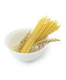 Spaghetti noodles and ears of wheat in white bowl Stock Images