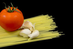 Spaghetti noodles with tomato and garlic. Spaghetti noodles with tomato and noodles isolated on the black background Royalty Free Stock Photo