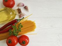 Spaghetti, oil, garlic, tomatoes on a wooden cuisine  frame. Spaghetti oil garlic tomatoes on a wooden frame cuisine Royalty Free Stock Image
