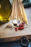 Spaghetti, olijfolie, knoflook en Spaanse pepers Stock Foto