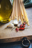 Spaghetti, olive oil, garlic and chilli. Spaghetti cooking ingredients on cutting board Stock Photo
