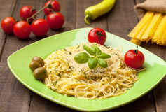 Spaghetti with olives and basil. On green plate Stock Photo