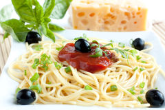 Spaghetti with olives and tomato sauce on plate Stock Photography