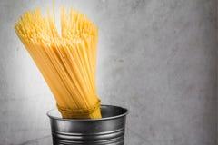 Spaghetti ongekookt in emmer stock fotografie