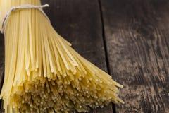 Spaghetti op een houten lijst Stock Afbeeldingen