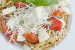 Spaghetti with parmesan and fresh tomatos. And basil Royalty Free Stock Image