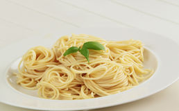 Spaghetti pasta with basil herbs. White background. Close up view. Royalty Free Stock Image