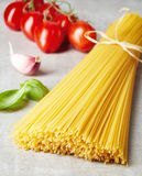 Spaghetti pasta, cheese and vegetables on grey stone table Stock Photos