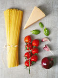 Spaghetti pasta, cheese and vegetables on grey stone table, top Stock Images