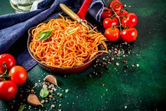 Spaghetti pasta with classic marinara tomato sauce. Italian lunch. Homemade spaghetti pasta with classic marinara tomato sauce, spices, garlic, basil. On a dark royalty free stock images