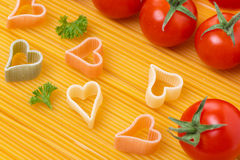 Spaghetti and pasta in the form of heart, selective focus Stock Photos