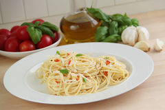 Spaghetti pasta with garlic, olive oil, chilly peppers and basil herbs. Ingredients on background. Close up view. Stock Image