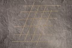 Spaghetti pasta on grey working surface arranged for tick tack toe.  Stock Photo