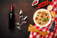 Spaghetti pasta with meatballs, cherry tomato sauce, cheese, wineglass and bottle on rusty background royalty free stock photos