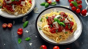 Spaghetti pasta meatballs with tomato sauce, basil, herbs parmesan cheese on dark background.  Stock Image