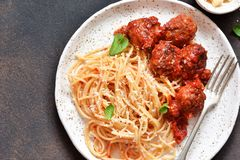 Spaghetti pasta with meatballs, tomato sauce and parmesan on the kitchen table. View from above. Spaghetti pasta with meatballs, tomato sauce and parmesan on the royalty free stock photography