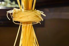 Spaghetti pasta nests and stand upright on a kitchen illuminated Stock Photos