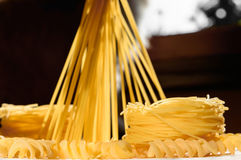 Spaghetti pasta nests and stand upright on a kitchen illuminated Stock Images