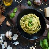 Spaghetti pasta with pesto sauce, basil, pine nuts and parmesan close up stock photo