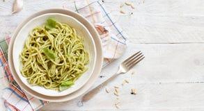 Spaghetti pasta with pesto sauce. Basil, pine nuts and parmesan close up stock photography