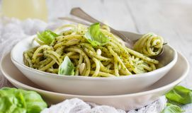 Spaghetti pasta with pesto sauce. Basil, pine nuts and parmesan close up royalty free stock photography