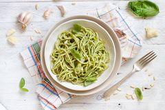Spaghetti pasta with pesto sauce. Basil, pine nuts and parmesan top view royalty free stock images