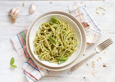 Spaghetti pasta with pesto sauce. Basil, pine nuts and parmesan top view stock images