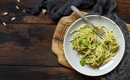 Spaghetti pasta with pesto sauce. Basil, pine nuts and parmesan top view stock photo
