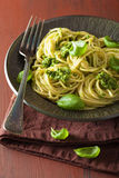 Spaghetti pasta with pesto sauce over rustic table Stock Images