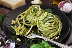 Spaghetti pasta with pesto sauce. Basil, pine nuts and parmesan close up stock photo