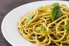Spaghetti pasta with pesto sauce. On black background. Close up stock images
