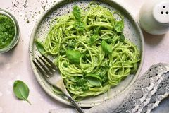 Spaghetti pasta with pesto sauce - traditional dish of italian c. Uisine on a plate over light slate, stone or concrete background.Top view royalty free stock photo