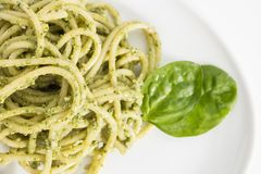 Spaghetti pasta with pesto sauce in white dish, closeup on white background. Spaghetti pasta with pesto sauce in white dish, closeup on white background Royalty Free Stock Image