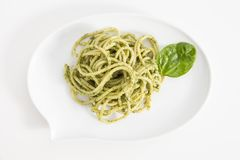 Spaghetti pasta with pesto sauce in white dish in shape of a chat bubble, on white background. Spaghetti pasta with pesto sauce in white dish in shape of a chat Royalty Free Stock Images