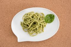 Spaghetti pasta with pesto sauce in white dish in shape of a chat bubble, on cork background. Spaghetti pasta with pesto sauce in white dish in shape of a chat Stock Image