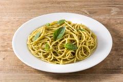 Spaghetti pasta with pesto sauce. On wooden table royalty free stock photos