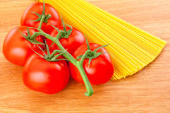 Spaghetti pasta and ripe tomatoes at branch close-up on wooden board. Bunch of spaghetti pasta and ripe tomatoes at branch close-up on wooden board Royalty Free Stock Images