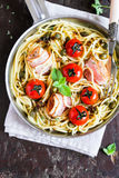Spaghetti pasta with roasted cherry tomatoes, bacon slices, capers and herbs in a pan ready to serve Royalty Free Stock Photos