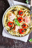 Spaghetti pasta with roasted cherry tomatoes, bacon slices, capers and herbs in a pan ready to serve Stock Photography