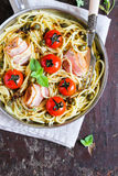 Spaghetti pasta with roasted cherry tomatoes, bacon slices, capers and herbs in a pan ready to serve Stock Photo