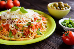 Spaghetti pasta salad with tomato sauce, olives, Gouda cheese and basil Royalty Free Stock Image