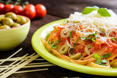 Spaghetti pasta salad with tomato sauce, olives, Gouda cheese and basil Stock Photos