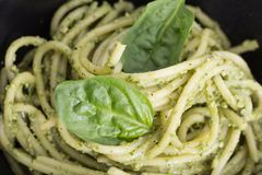 Spaghetti pasta with sauce pesto in black bowl, closeup background. Stock Image