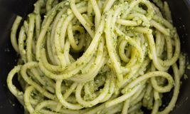 Spaghetti pasta with sauce pesto in black bowl, closeup background. Spaghetti pasta with sauce pesto in black bowl, closeup background Royalty Free Stock Photo